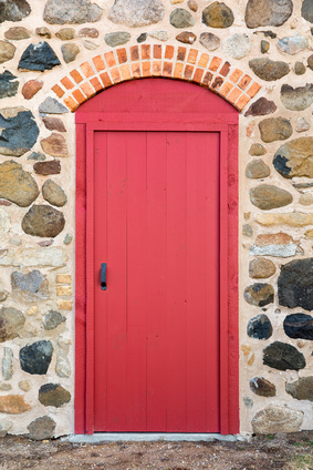 Bright Red Arched Door in a Stone Wall